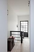 Holzhocker im Designerstil im Treppenhaus mit verglaster Tür