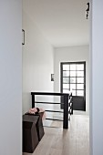 Designer-style wooden stool in stairwell with glazed door