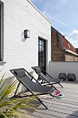 Two deckchairs on sunny, wooden roof terrace adjoining whitewashed brick façade