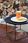 Beaker of coffee and waffles on charcoal tray table on animal skin rug in front of stacked firewood