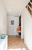 Teenager sitting on classic chair in workspace with folding door cleverly integrated under staircase in hallway