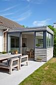 Holzverschalter, eingeschossiger Anbau für Wohnküche, davor ein Essplatz auf sonniger Terrasse