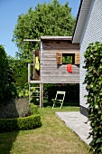 Wooden playhouse on stilts in garden surrounded by tall hedge; whitewashed brick facade to one side
