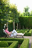 Boy sitting on deckchair amongst geometric box hedges in garden surrounded by espalier trees and tall hedges