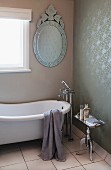 Oval mirror with ornate metal frame, vintage bathtub and floor-mounted taps in bathroom with rolled paint pattern on wall