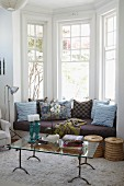 Window seat with many cushions in bay window behind glass coffee table on flokati rug