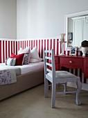 Hellgrau lackierter Stuhl vor rotem Schreibtisch, daneben Bett vor halbhoch, rotweiss gestreifter Wand