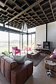 Leather sofa set and pink armchairs around block-style coffee table next to glass wall with view of landscape