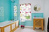 Bad mit hellblauen Wandfliesen, seitlich Badewanne mit Holzverkleidung, im Hintergrund Fenster mit gemustertem Rollo, und Waschbecken mit Holzunterschrank