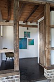 Doorway between wooden support pillars in foyer with rustic wooden ceiling and modern artworks