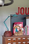 Türkisfarbene Vintage Tischleuchte neben Büchern und moderner, farbenfroher Zeichnung auf nostagischem Schubladenschrank