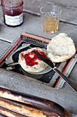 Bread roll and jam on rustic table