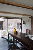 Lange Holztheke und Vintage Barhocker in renoviertem Landhaus mit Fensterfront und Retrosesseln mit Schaffell
