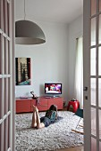Girl lying on grey flokati rug, pendant lamp and low, red sideboard
