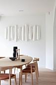 Moderner Essplatz mit Stühlen und Tisch aus hellem Holz, an Wand aufgehängtes Kunstobjekt in Weiss
