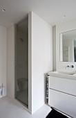Ausschnitt eines Waschtisches mit weißem Unterschrank neben gemauertem Duschbereich und Glastür