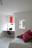 Bunte Streifenkissen auf Bett, im Hintergrund Arbeitsplatz am Fenster, Klassikerstuhl mit dunkler Sitzschale