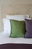 Kissen auf Bett mit weissen Bettbezügen vor beige marmoriertem Hintergrund