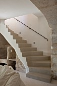 Curved concrete staircase with wrought iron handrail in Provençal stone house