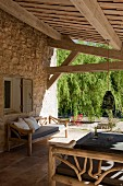 Outdoor furniture made from branches on roofed terrace adjoining Provençal stone house
