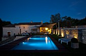 Twilight atmosphere around illuminated pool outside traditional, renovated country house