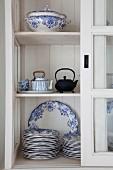 Blau-weisse Teller und Terrine und asiatische Teekannen in Vitrinenschrank mit offener Schiebetür