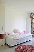 Round, colourful rug in front of white bed on castors with storage drawer in bright, girl's bedroom