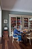 Mann im Armlehnstuhl am Holztisch, antiker Vitrinenschrank an grau getönter Wand im Wohnzimmer