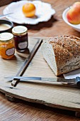 Cut loaf, knife and jars of jam on wooden board