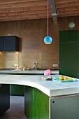 Blaue Kugelleuchte über geschwungener Kochinsel mit grünen Unterschränken; Küchenrückwand mit Messingplatten