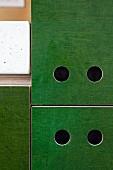 Detail einer selbstgebauten Küchenzeile mit Grifflöchern in grün lasierten Küchenfronten