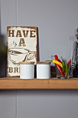 Vintage advertising sign, china pots and glass of chilli peppers on narrow kitchen shelf