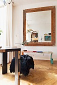 Table and bench made from book bindings and large, framed mirror on wall