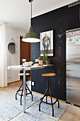 Vintage swivel stools and breakfast bar against black wall below pedant lamps with green metal lampshade