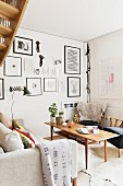 Wooden coffee table between fifties-style armchair and sofa in corner of living room; gallery of framed pictures on wall