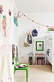 Bemalte Zimmertür, grüner Stuhl und einzelne Regalmodule auf Holzboden im Kinderzimmer