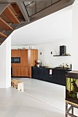 View from platform into open-plan kitchen with black base units in minimalist interior