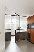 Wooden kitchen cupboards with fitted appliances next to glass and metal door element