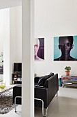 Modern, black leather couch behind pillar; large portraits on wall