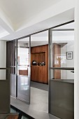 Glass and metal partition with door leading to hallway