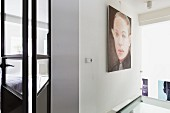Large portrait on wall next to open, glass and metal door