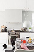 Set breakfast table below pendant lamp with pale lampshade and kitchen counter in background