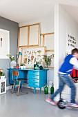Blick in Nische auf blau lackierten Schreibtisch und Stuhl im Retro Stil, davor vorbeifahrendes Kind auf Roller
