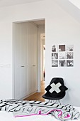 Striped bedspread on bed, cushion on classic, black shell chair and fitted wardrobes in doorway passage
