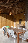 Outdoor kitchen - long wooden table and white metal chairs on rustic, roofed terrace with wood-clad walls