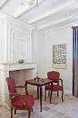 Antique armchairs and Rococo-style side table in front of fireplace in Mediterranean interior