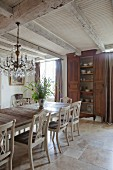 White-painted kitchen chairs with carved backrests around wooden table; crockery in cupboard in background in rustic dining room with wood-beamed ceiling