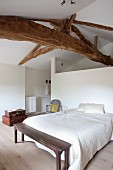 Double bed against partition and simple wooden bench at foot of bed in white bedroom with rustic, wooden ceiling beams