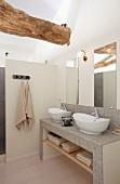 Gemauerter Waschtisch mit Mosaikfliesen und weissen Schüsseln, vor Spiegel an Wand, in renoviertem Bad mit teilweise sichtbarem Holzbalken