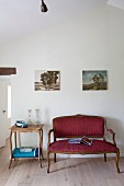 Rococo couch with red cover and side table below landscapes on wall